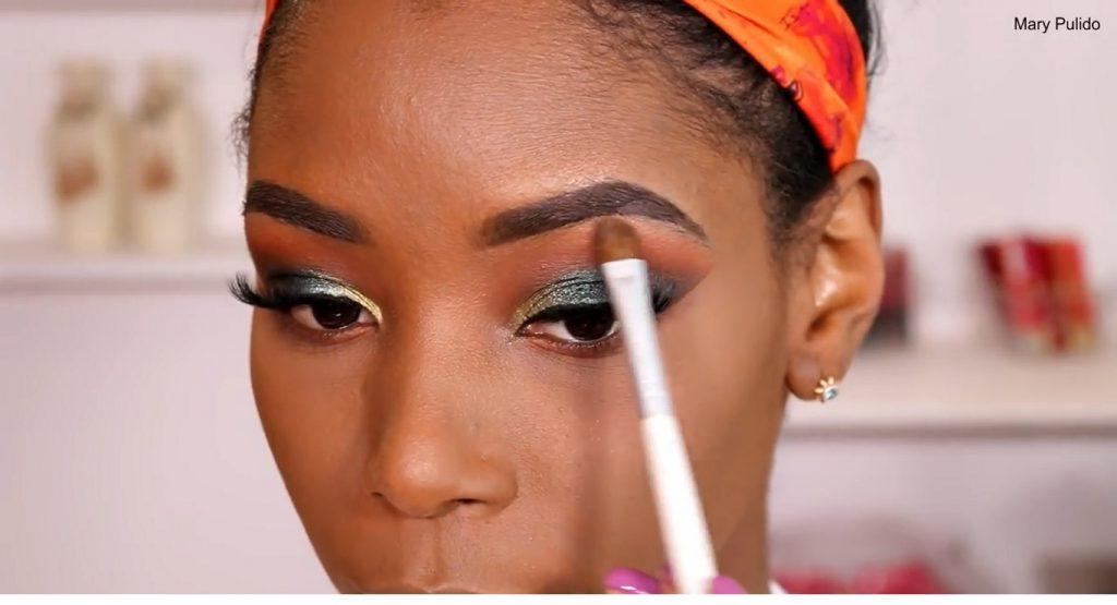 Tutorial de maquillaje de noche para piel morena aplicar iluminador en los párpados
